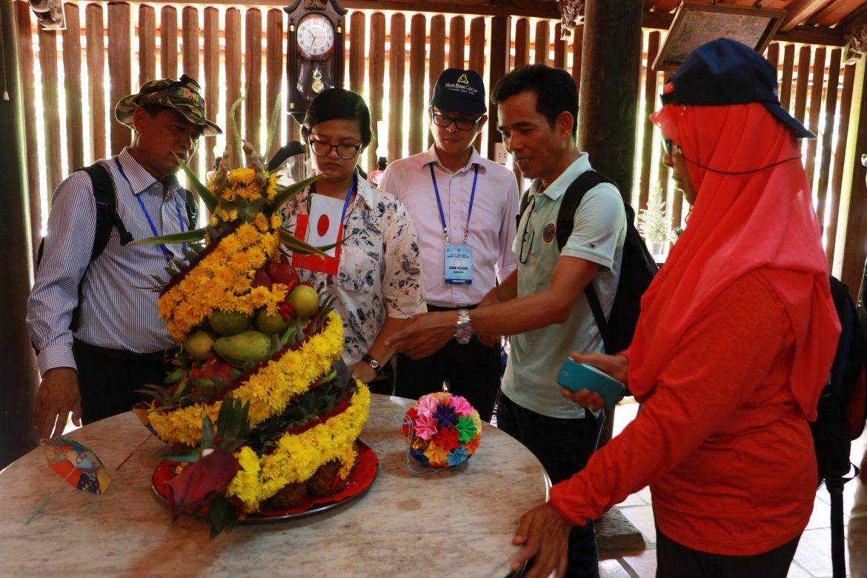 Anh Vũ (thứ hai từ phải sang), một hướng dẫn viên du lịch, giải thích với du khách nước ngoài về cách trang trí mâm cỗ bằng trái cây tại Việt Nam